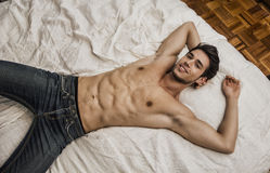 Shirtless sexy male model lying alone on his bed. Shirtless sexy young smiling man lying alone on his bed in his bedroom, looking at camera with a seductive Stock Photos