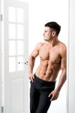 Shirtless sexy male model standing in the doorway home interior, looking away with a seductive attitude Royalty Free Stock Photography