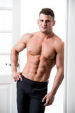 Shirtless sexy male model standing in the doorway home interior, looking to camera with a seductive attitude Royalty Free Stock Photos