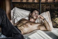 Shirtless sexy mannelijk model die alleen op zijn bed liggen Royalty-vrije Stock Foto