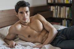 Shirtless sexy mannelijk model die alleen op zijn bed liggen Royalty-vrije Stock Afbeeldingen