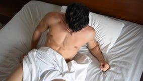 Shirtless sexy mannelijk model die alleen op zijn bed liggen stock video