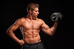 Shirtless sexy muscaular sportsman pumping up biceps with black dumbbell Royalty Free Stock Photos