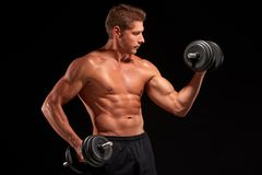 Shirtless sexy muscaular sportsman pumping up biceps with black dumbbells Royalty Free Stock Photography