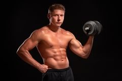 Shirtless muscular sportsman pumping up biceps with black dumbbell Stock Photos