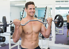 Shirtless smiling bodybuilder lifting heavy barbell weight Stock Image