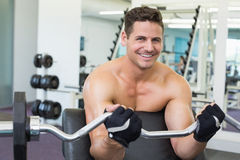 Shirtless smiling bodybuilder lifting heavy barbell weight using bench Royalty Free Stock Photo