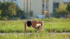 Shirtless sportmanopdrukoefeningen op sportenringen bij atletisch gebied stock videobeelden