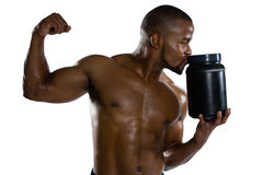 Shirtless sports man kissing supplement jar. While flexing muscles Stock Images