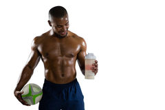 Shirtless sportsman with rugby ball holding drinking bottle. While standing against white background Stock Photos