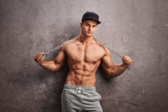 Shirtless street thug holding a metal chain. Shirtless street thug stretching a metal chain over his shoulders and leaning against a rusty gray wall Royalty Free Stock Images