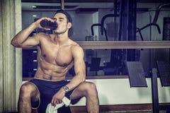 Shirtless ung man som dricker proteinskakan i idrottshall royaltyfri bild