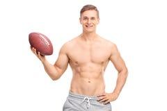 Shirtless ung man som rymmer en fotboll royaltyfri fotografi