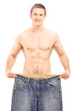 Shirtless weightloss male showing his old pair of jeans Stock Photo