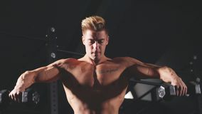 Shirtless white man starting exercise with dumbbell weight in dark gym. Shirtless white man in sweatpants starting exercise with dumbbell weight in dark gym stock footage
