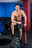 Shirtless young athlete with sledgehammer in gym Stock Photos