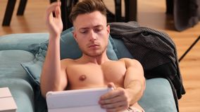 Shirtless young athletic man reading on ebook reader. Shirtless young athletic man holding ebook reader or tablet PC and reading while sitting on couch stock footage