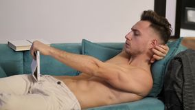 Shirtless young athletic man reading on ebook reader. Shirtless young athletic man holding ebook reader or tablet PC and reading while sitting on couch stock video
