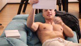 Shirtless young athletic man reading on ebook reader. Shirtless young athletic man video chatting with tablet PC smiling for the camera while sitting on couch stock video