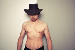 Shirtless young cowboy against dual colored background Stock Photos