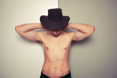 Shirtless young cowboy against dual colored background Royalty Free Stock Photography