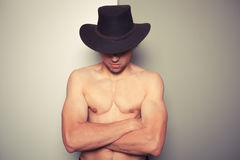 Shirtless young cowboy against dual colored background Royalty Free Stock Photo