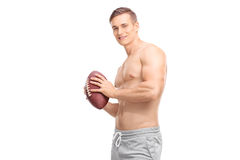 Shirtless young guy holding a football stock photos