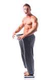 Shirtless young male bodybuilder has lost weight. Wearing large pants. Smiling, isolated on white Royalty Free Stock Photo