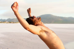 Shirtless young man with arms raised Stock Photo