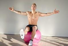 Shirtless young man balancing on fitness ball Stock Images