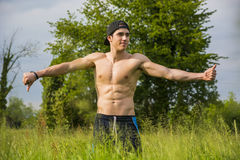Shirtless young man doing funny pose standing Royalty Free Stock Photo