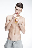 Shirtless young man drinking orange juice Stock Photo