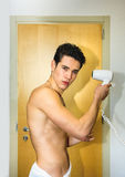 Shirtless young man drying hair with hairdryer Royalty Free Stock Images