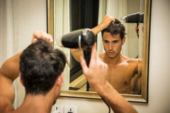 Shirtless young man drying hair with hairdryer Stock Image