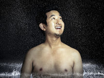 Shirtless young man enjoying rain Stock Photo