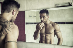 Shirtless young man examining his stubble in mirror Royalty Free Stock Photography