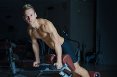 Shirtless young man exercising femural biceps on gym equipment Stock Photos
