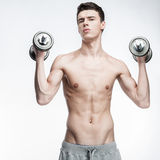 Shirtless young man holding dumbbells Stock Photography