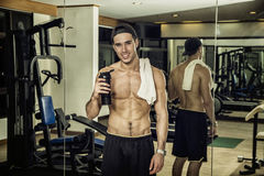 Shirtless young man holding protein shake in gym Stock Image
