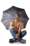 Shirtless young man holding umbrella and looking up. Sitting on floor, isolated on white Stock Photography