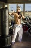 Shirtless young man kicking punching bag Royalty Free Stock Photos