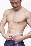 Shirtless young man measuring waist Stock Image