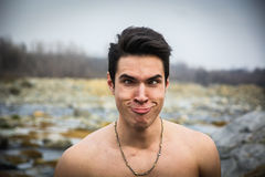 Shirtless young man outdoor doing silly face Stock Photography