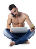 Shirtless young man overwhelmed by technology: PC, tablet, phones Royalty Free Stock Image