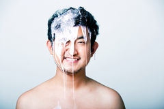 Shirtless young man with pink paint falling on his head against gray background Royalty Free Stock Photo