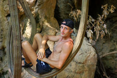 Shirtless young man relaxing and leaning against tree or a liana in front of cave Stock Image