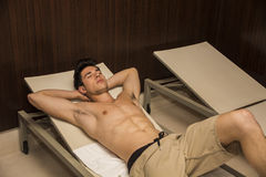 Shirtless Young Man Relaxing in Lounge Chair Royalty Free Stock Photo