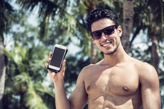 Shirtless Young Man Showing Cell Phone at Beach Royalty Free Stock Photos