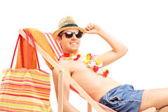 Shirtless young man sitting on a sun lounger stock photography