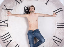 A shirtless young man is standing in front of a clock Royalty Free Stock Photo